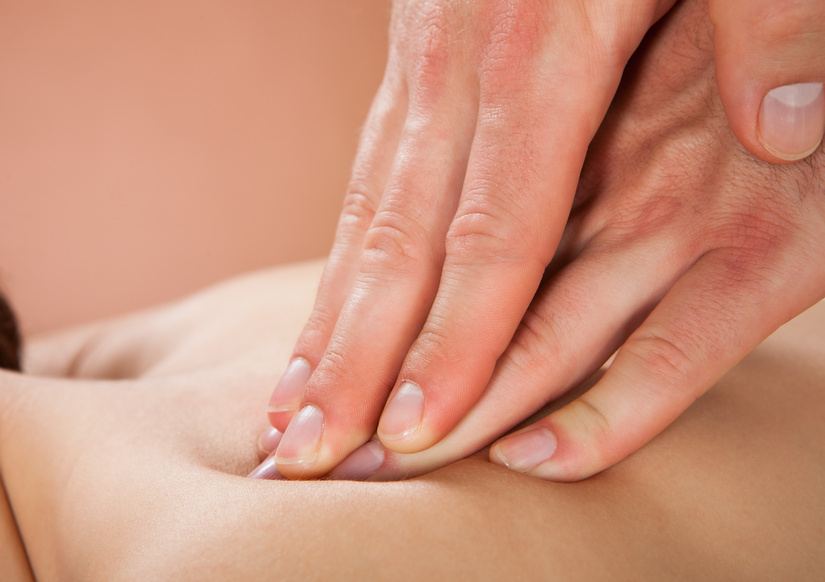 Therapist Massaging Female Customer's Back At Spa